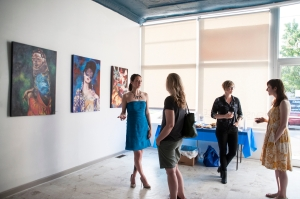 """Cindy Lisica with gallery visitors during the exhibition """"Great Waves"""" this summer. Photo by Gianna Paniagua."""
