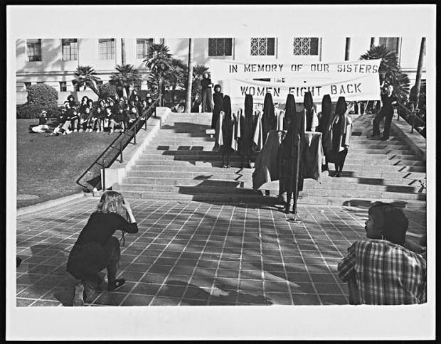 In Mourning and In Rage media performance at Los Angeles City Hall, December 13, 1977, Suzanne Lacy and Leslie Labowitz-Starus. Gelatin silver prints documenting the event by Susan Mogul. 7 15/16 x 10 3/16 in. The Getty Research Institute, Lawrence Alloway Papers, 2003.M.46. Photo copyrighted by Susan Mogul - (Image from http://blogs.getty.edu/pacificstandardtime/explore-the-era/worksofart/in-mourning-and-in-rage-media-performance-at-los-angeles-city-hall/)